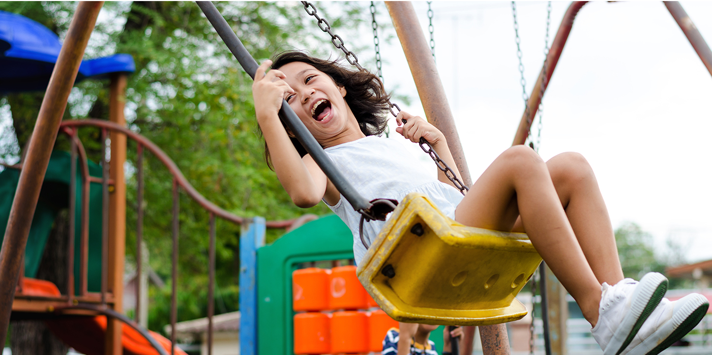 Happy young girl on a swing in a park