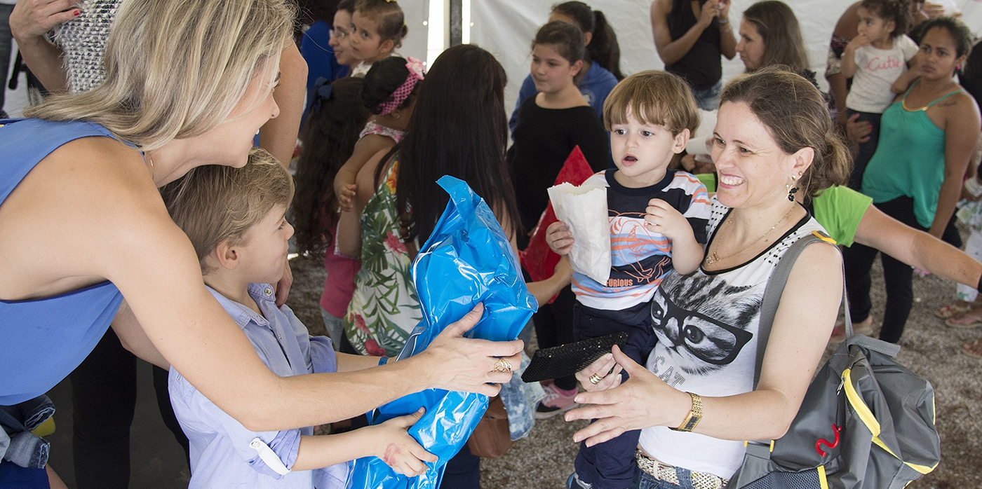 young person presenting a blue bag to parent of another young person