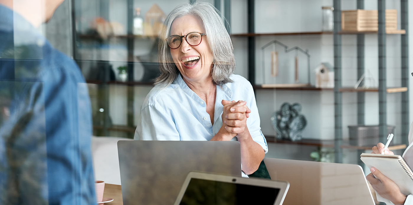 Happy lady sitting in front of laptop