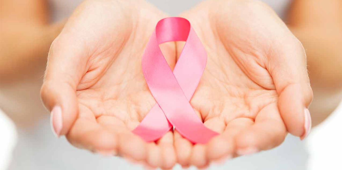 Pink breast cancer ribbon held in cupped hands