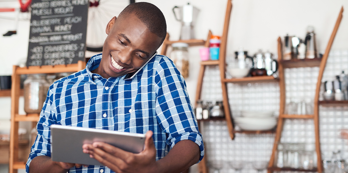 business owner on mobile phone and working on tablet device