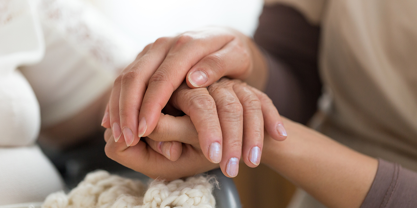 Carer holding hands of patient