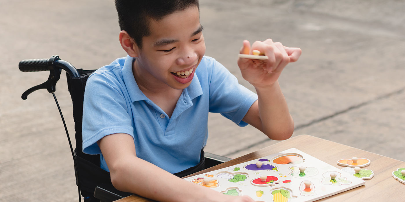 young person in a wheelchair playing games at a table