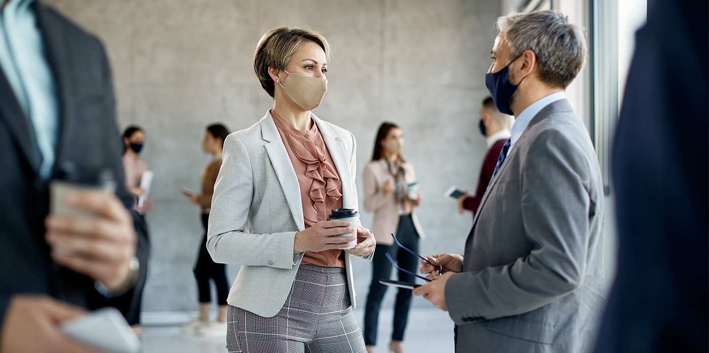 People with surgical masks on attending an indoor conference