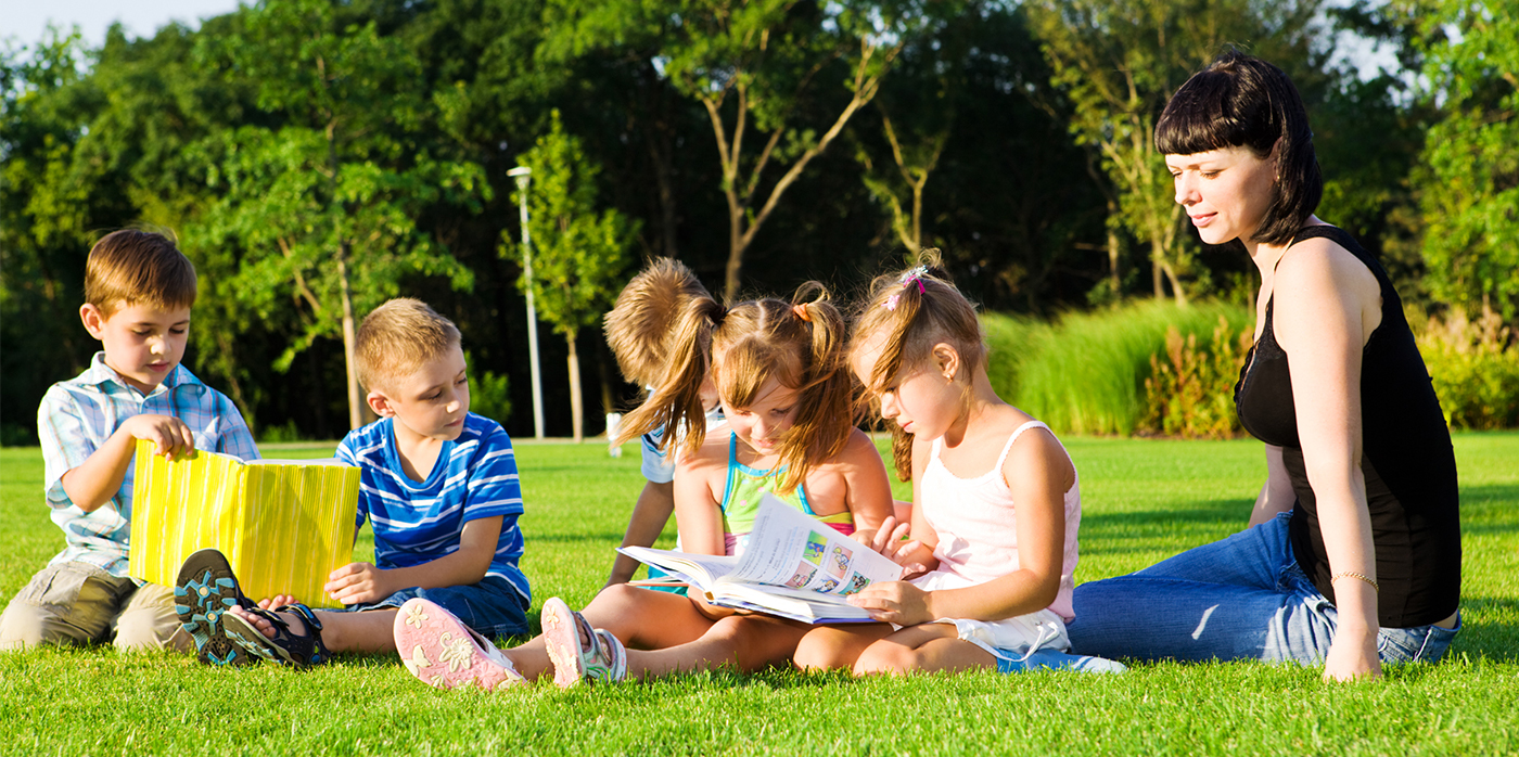 Group of young children sitting on the grass in a park