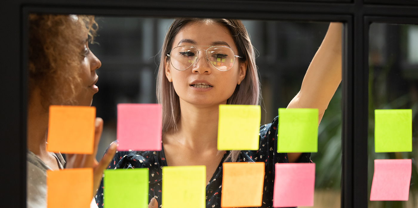 Woman looking at sticky notes on glass wall