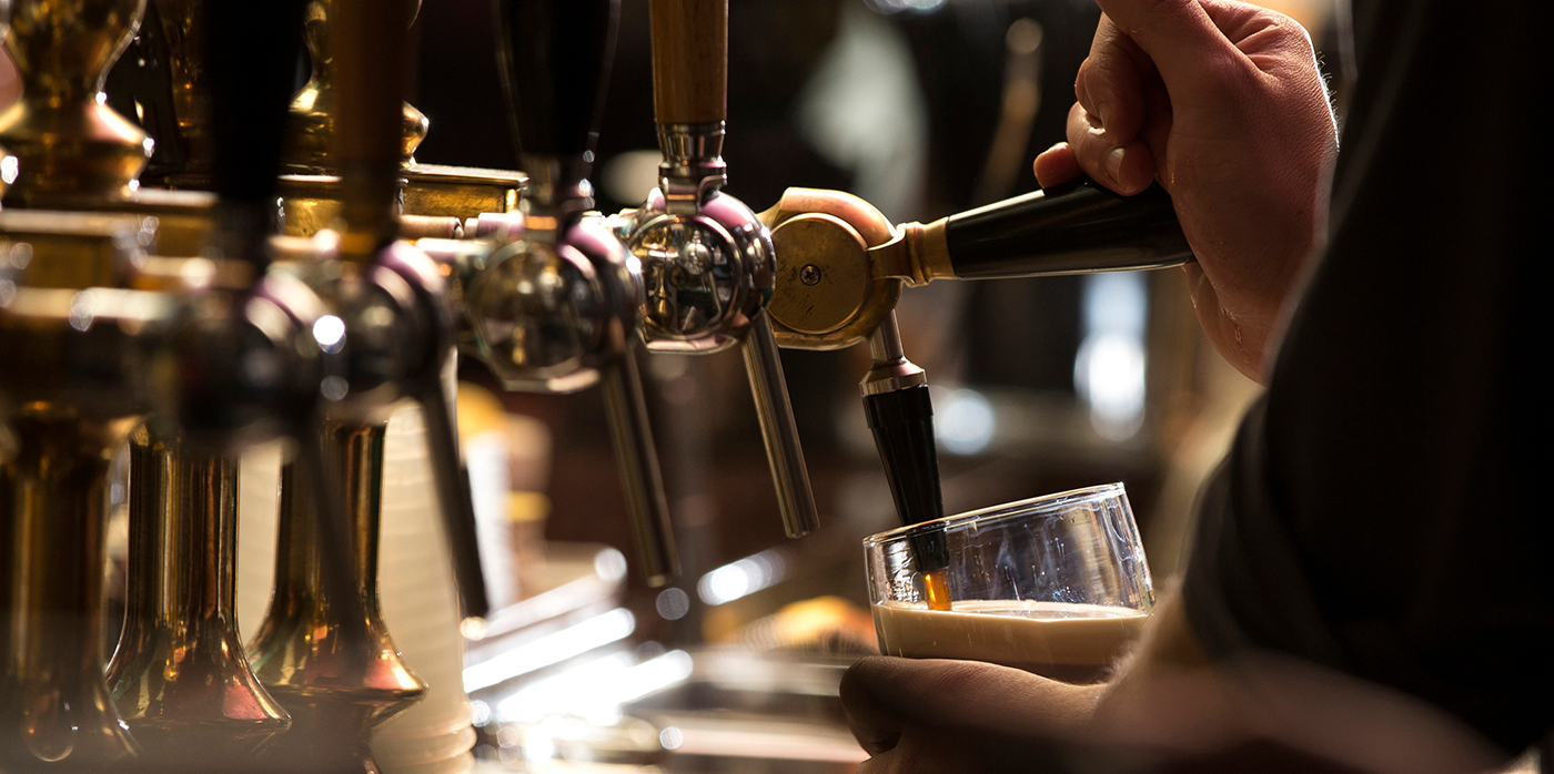 Close up of a man pouring a pint in a pub