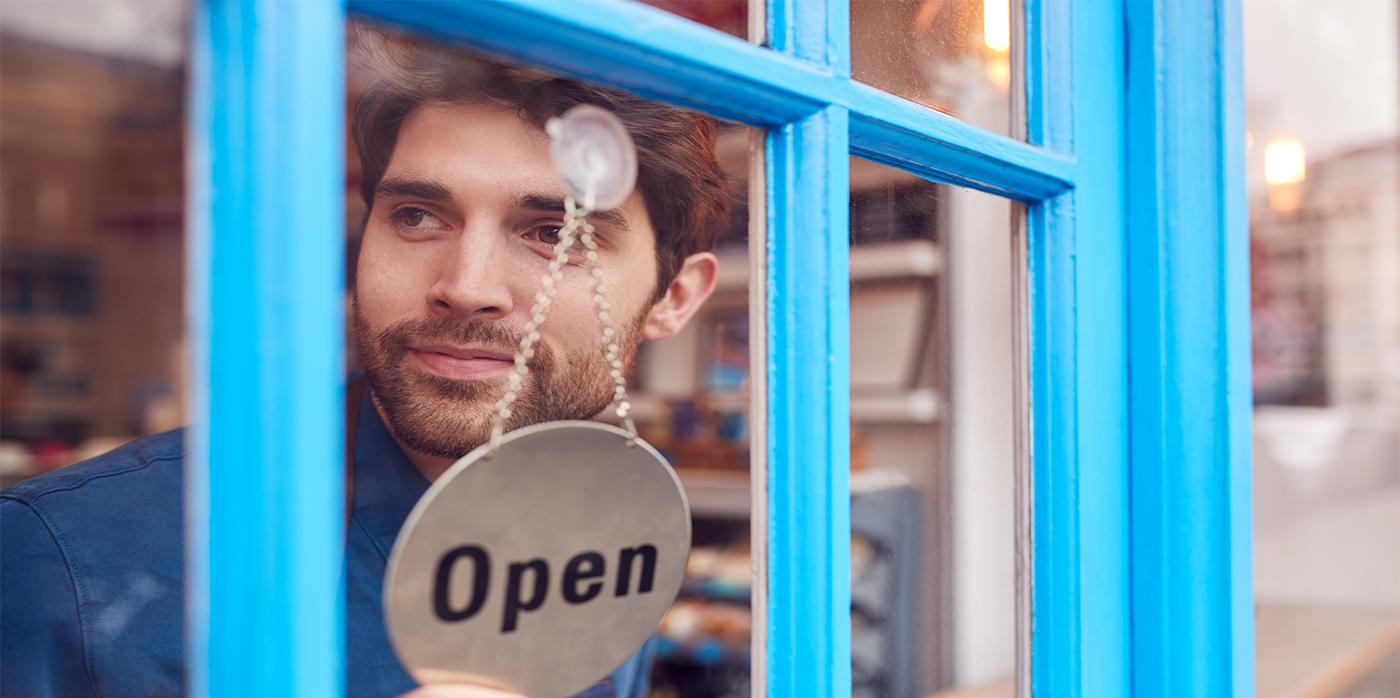 shop owner looking out of door behind open sign
