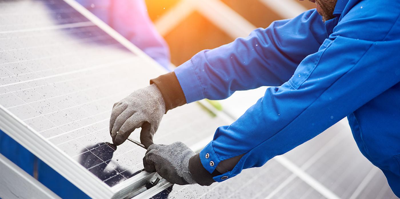 man fitting solar panel on house