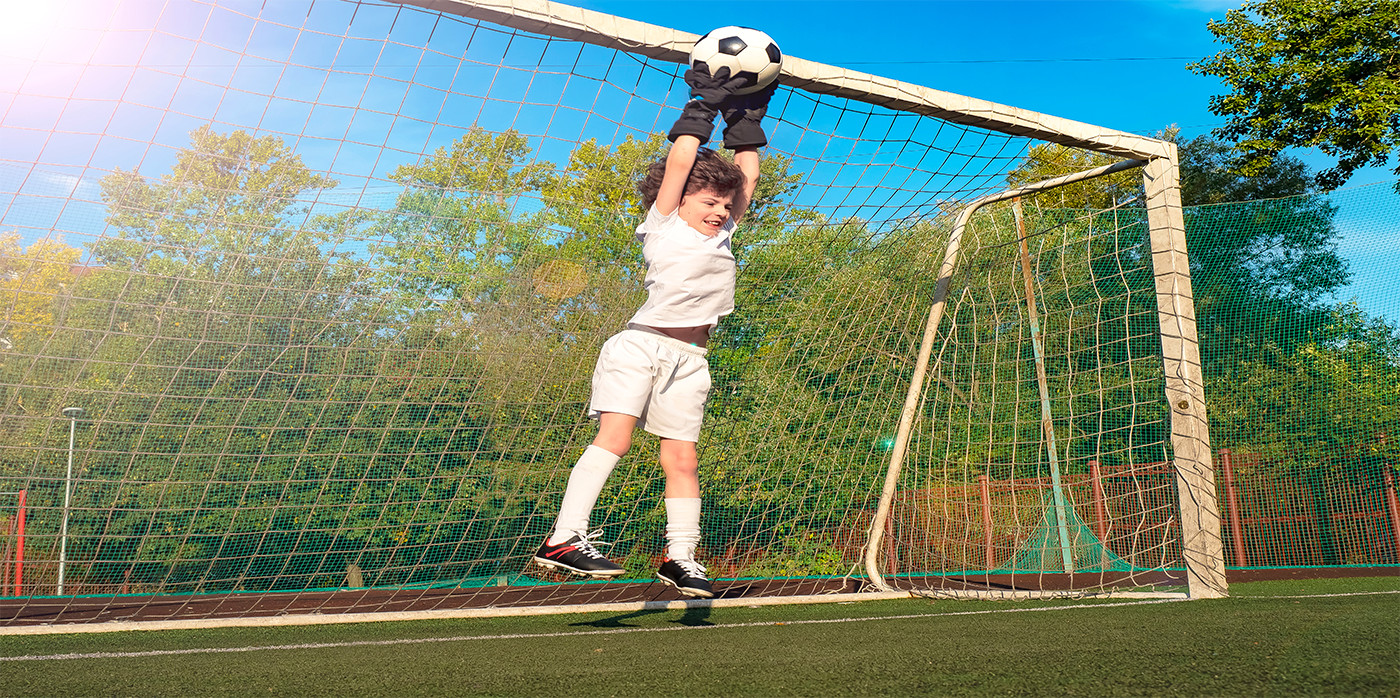 young person saving a goal on football pitch