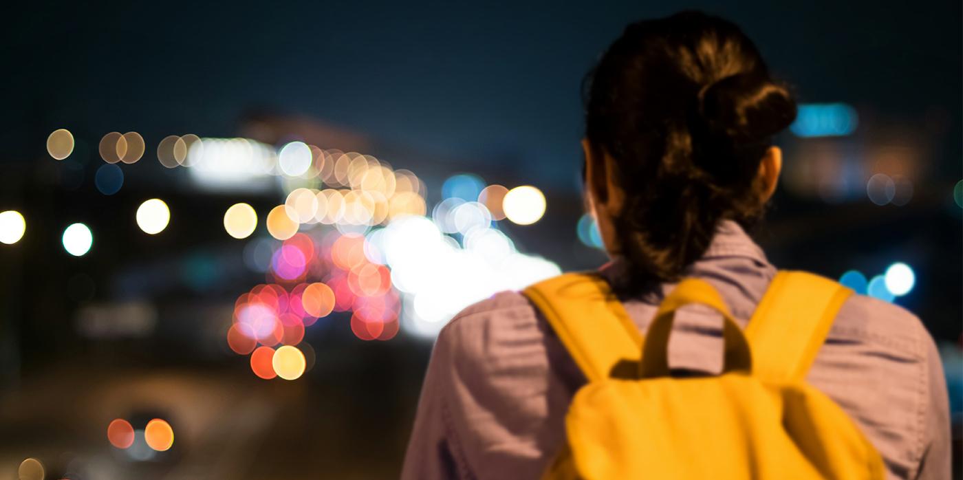 woman with yelloe rucksack walking along road at night